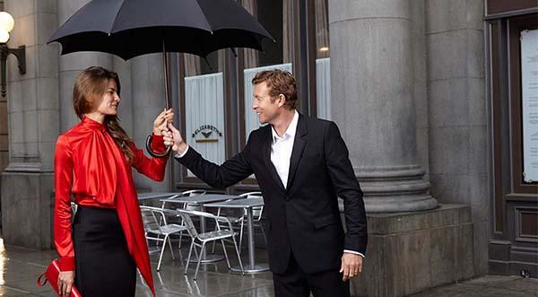 мужчина держит зонт над девушкой